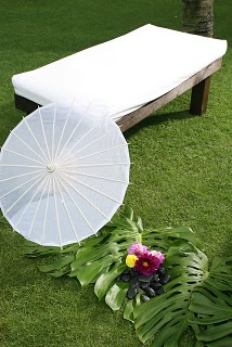 soothing white color seating like a bed and umbrella for theme wedding