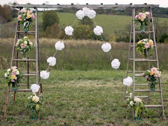 Simple wooden ladder can be turned into a beautiful archway with floral bouquets on the steps