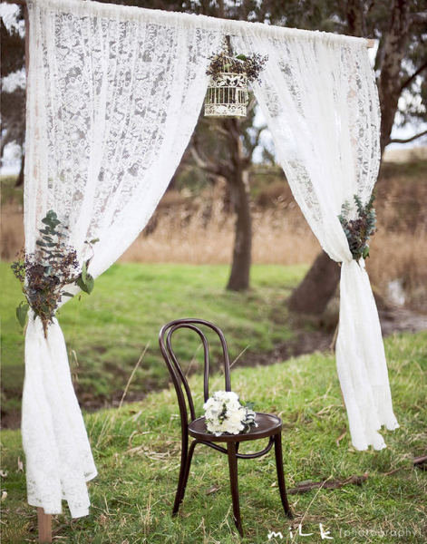 Dainty lace curtains, natural arrangements, and a delicate white birdcage create a rustic, elegant vibe.