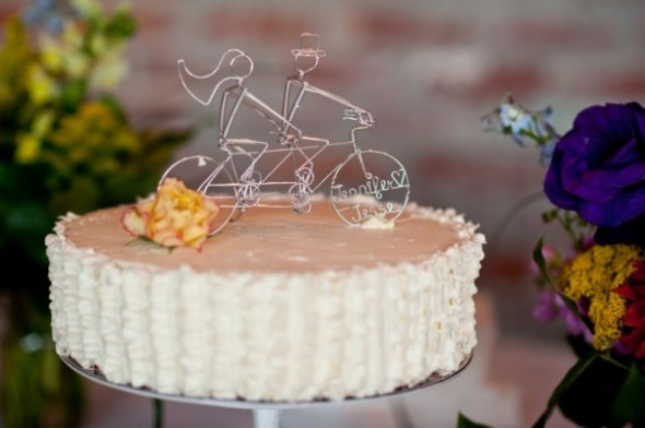 white wedding cake with bicycle cake topper.