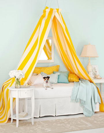 Make smart use of an embroidery hoop, attach ready made light weight curtains to the hoop and you have a canopy ready