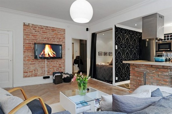 """A rustic brick wall acts as a """"decorative"""" border between the two rooms and ensures a high level of originality."""