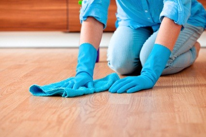 Close up of a woman's hands as she kneels on the floor wiping it with a rag.